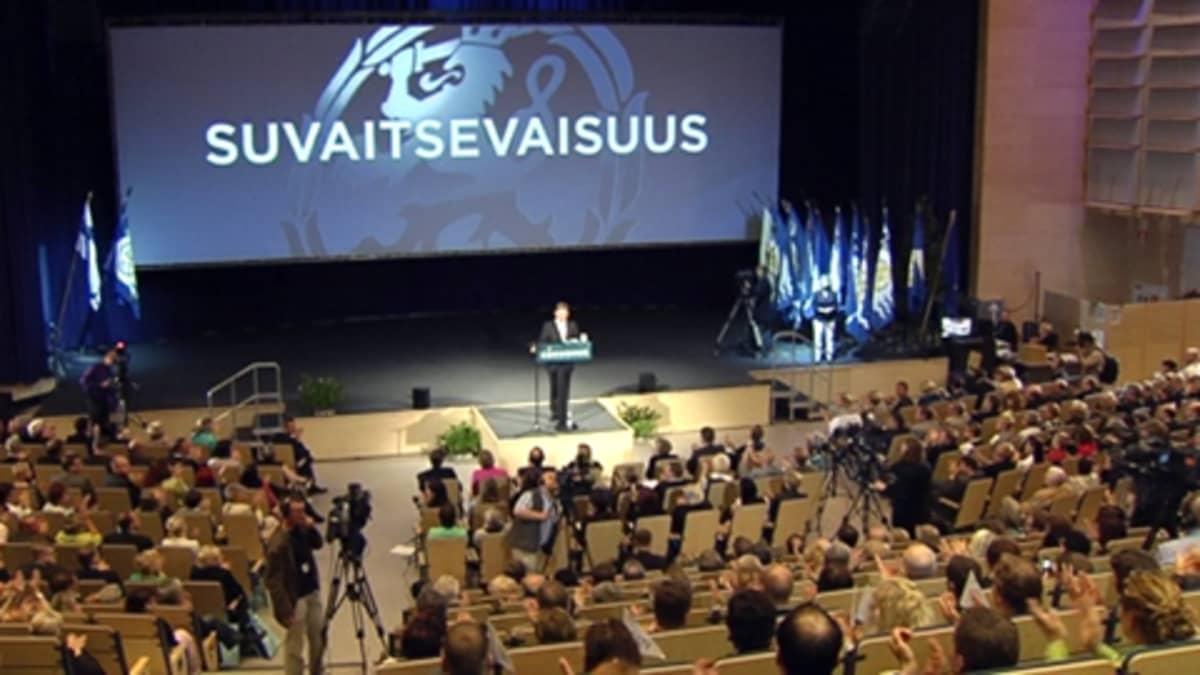 Kokoomuksen puheenjohtaja Jyrki Katainen puhuu puoluekokouksessa. Taustalla esitellään puolueen arvoja.