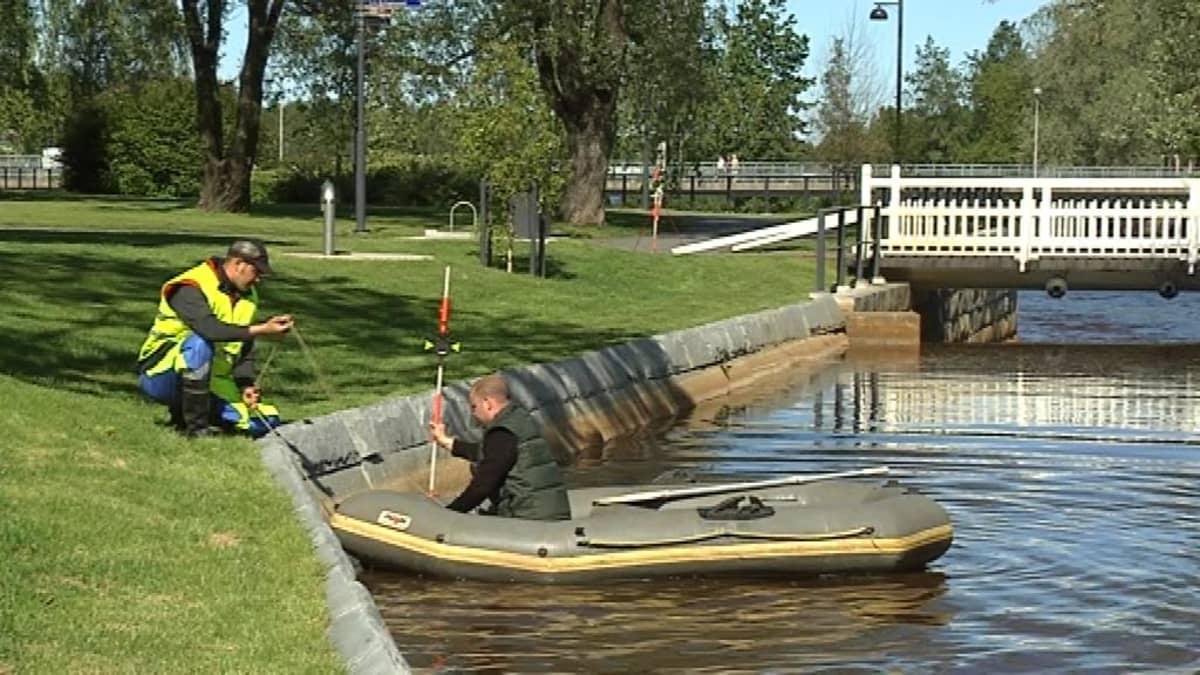 miehet mittaa joen syvyyttä