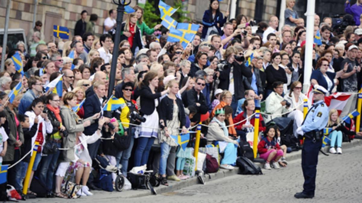Ihmiset heiluttavat Ruotsin lippujen kadun varrella Tukholmassa.