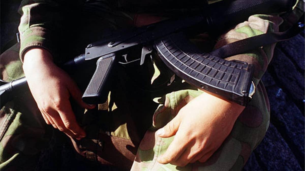 Puolustusvoimien sotilas rynnäkkökivääri sylissään
