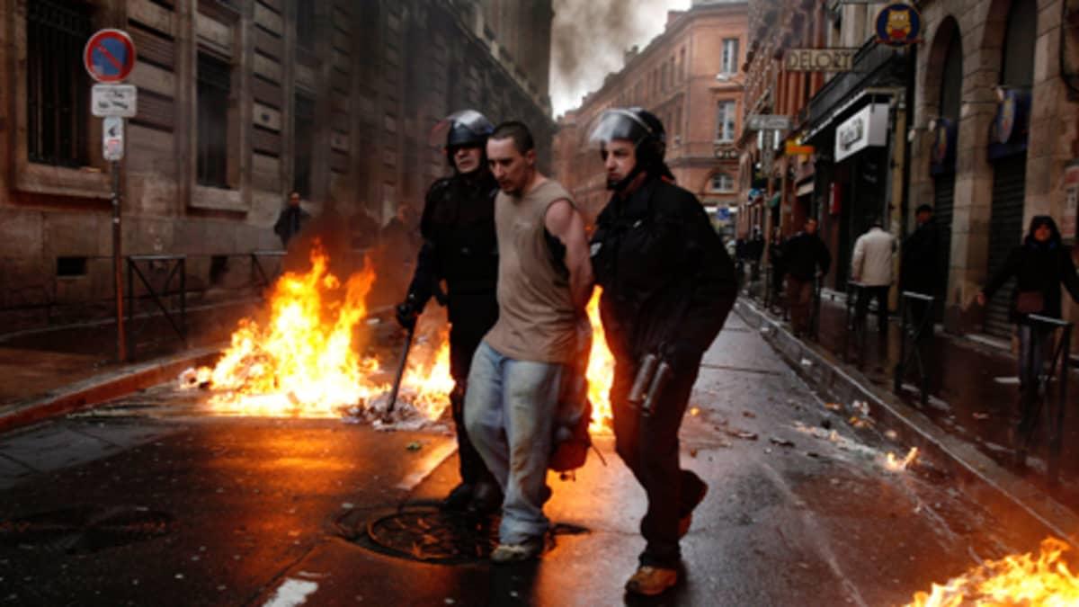 Kaksi mellakkapoliisia taluttaa mielenosoittajaa.