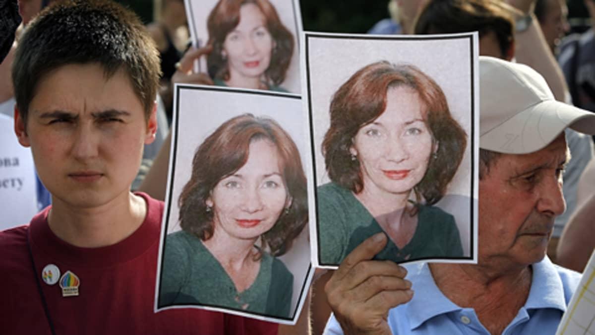 Ihmiset pitivät käsissään murhatun ihmisoikeusaktivistin Natalia Estemirovan kuvia