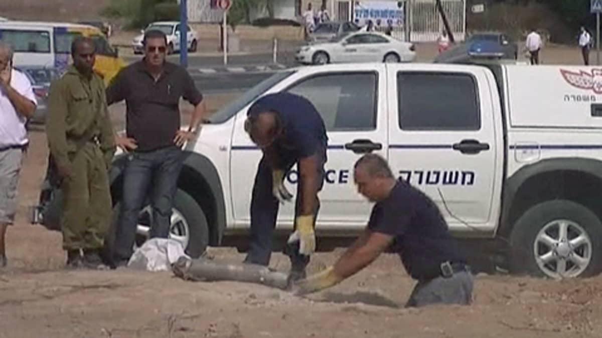 Poliisit nostavat räjähtäneen raketin sen synnyttämästä kuopasta.