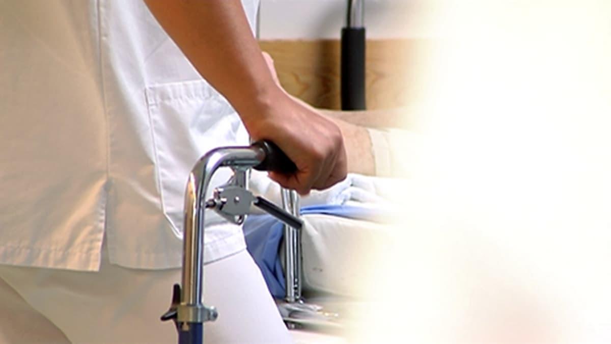 Hoitajan käsi pitää kiinni rollaattorista tai jostakin muusta metallisesta laitteesta, joka ei näy kokonaan kuvassa. Etualaa peittää vaaleassa takissa ohi kävelevä terveydenhoitaja.