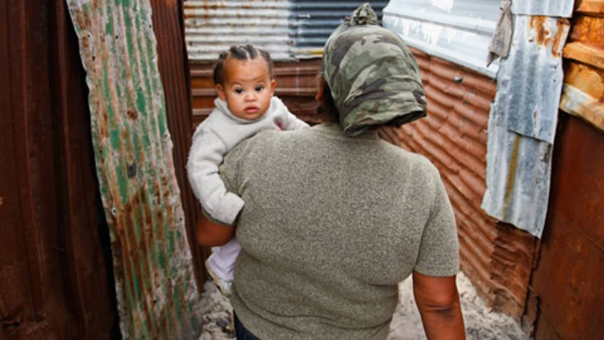 Hökkelikylässä asuva nainen kantaa lastaan