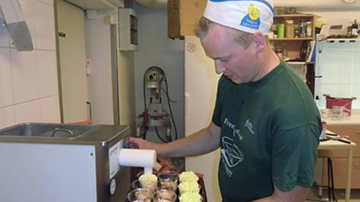 Mies pursottaa koneesta jäätelö kuppeihin