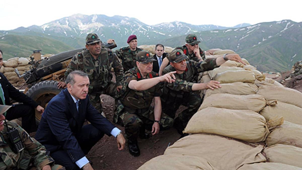 Miehiä hiekkasäkkien suojaamassa vartiopaikassa
