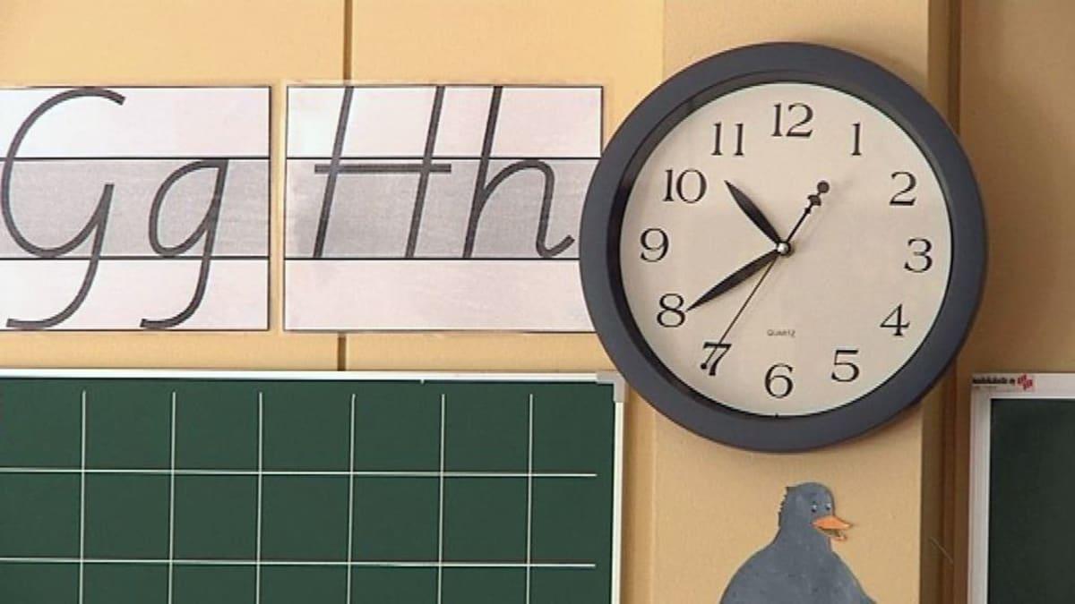 koulun kello, kirjainmalleja ja liitutaulu seinällä