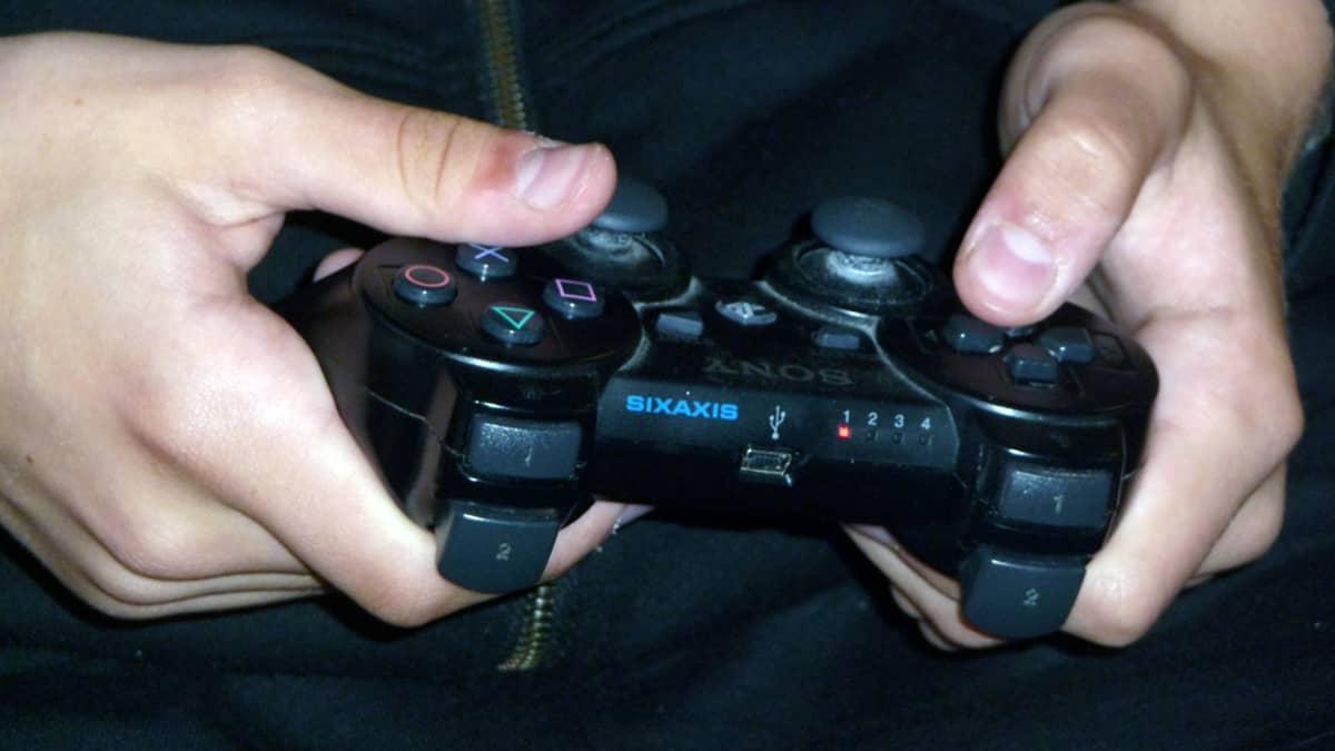 Nuori näppäilee Playstation-peliohjainta.