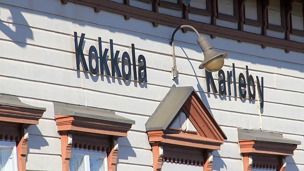 Kuvassa Kokkolan rautatieaseman Kokkola - Karleby -kyltti  pääoven päällä.