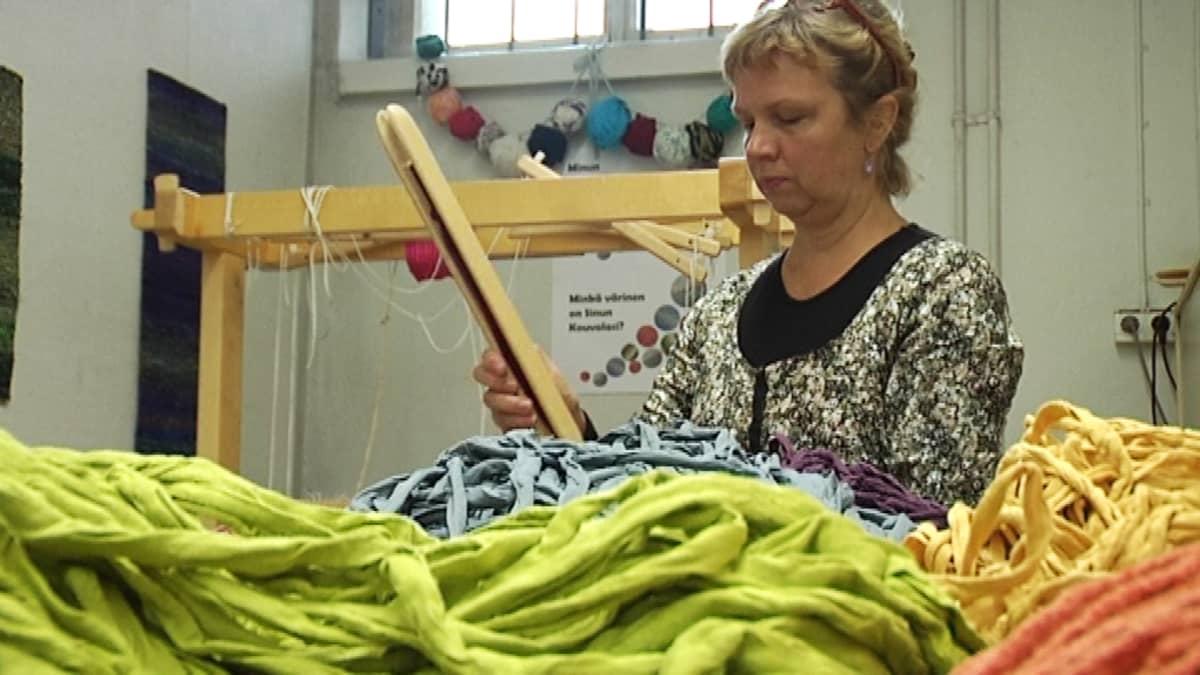 Nainen kutoo kangaspuilla.