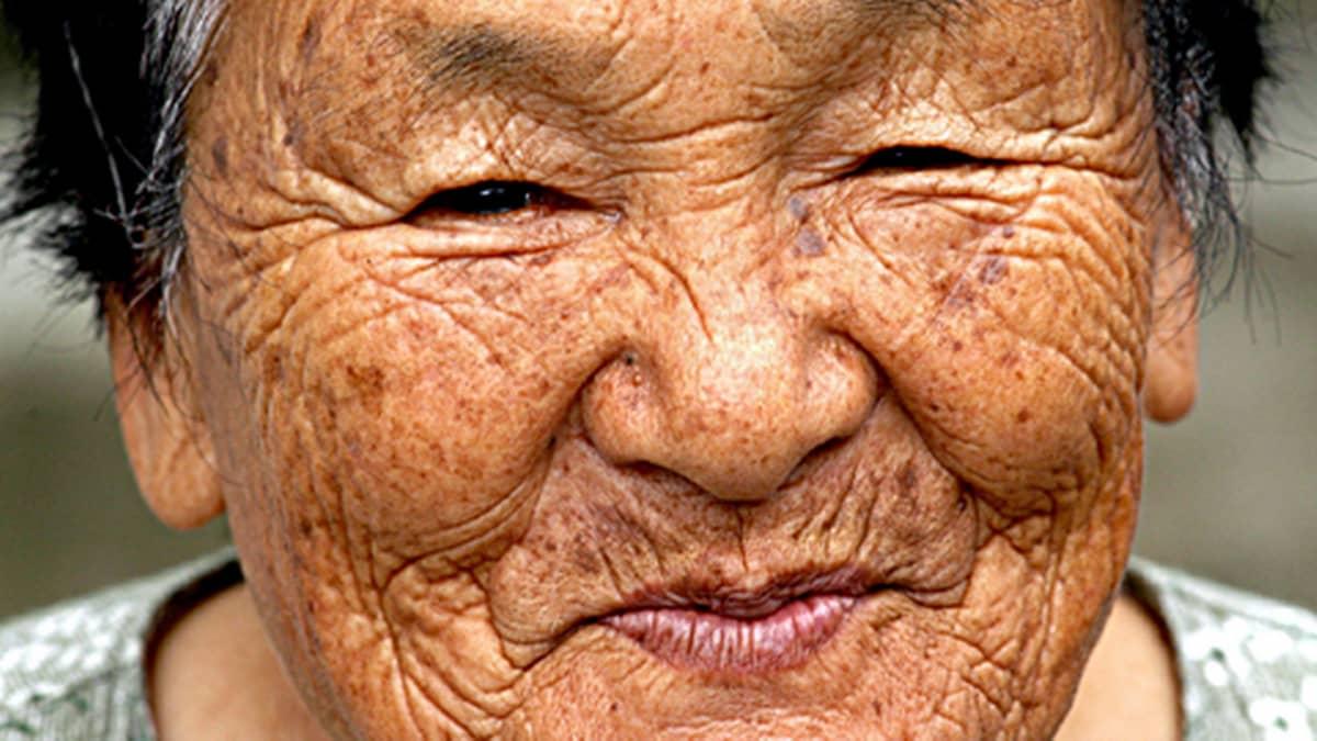 Ikääntyneen japanilaisnaisen hymyilevät kasvot.