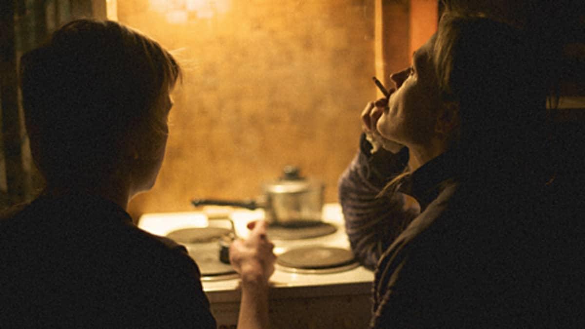 Ruutukaappaus elokuvasta Taulukauppiaat.  Kaksi miestä tupakoi sähköhellan ääressä.