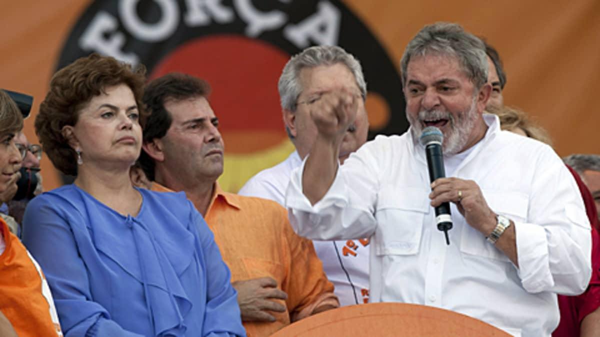 Kuvassa vasemmalla Brasilian entinen presidentti Lula da Silva ja nykyinen presidentti Dilma Roussef. He ovat lavalla. Lula puhuu.
