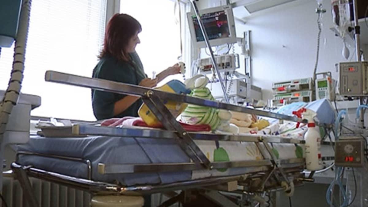 Hoitaja sairaan lapsen sängyn vieressä sairaalassa.