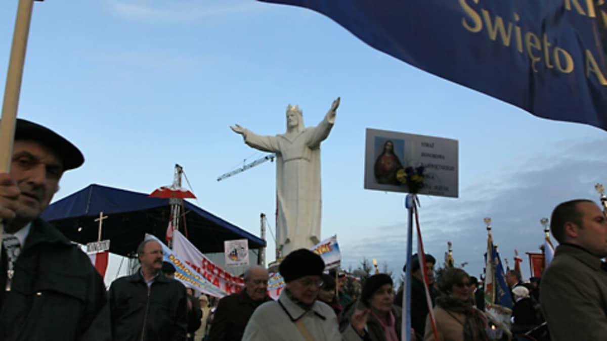 Ihmisiä patsaan paljastamistilaisuudessa, keskellä kuvaa näkyy kädet avoimeen kohotukseen nostanut Jeesus-patsas.