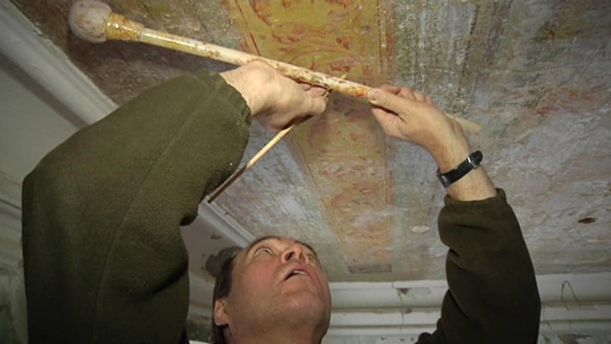 Maalarimestari maalaa koristemaalauksia.