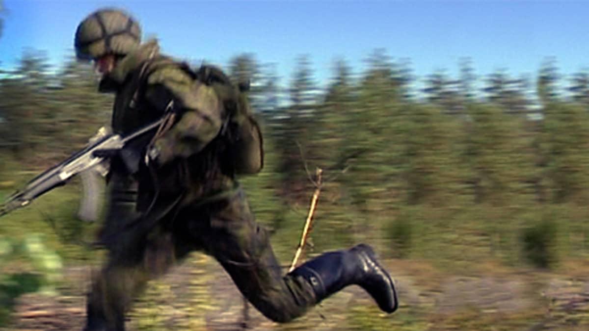 Sotilas juoksee metsässä kiväärin kanssa