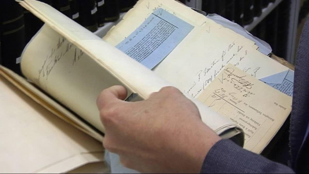 Vanhaa kirjaa selataan arkistossa.
