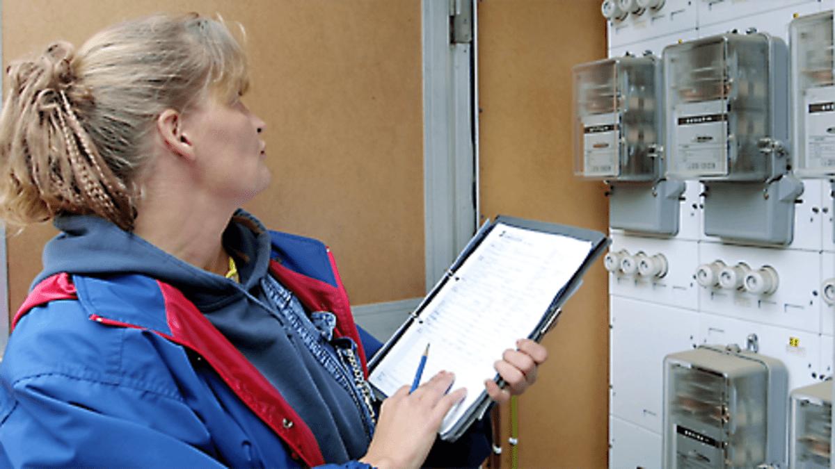Sähkölaitoksen mittarinlukija ottamassa lukemia ylös sähkötaulusta