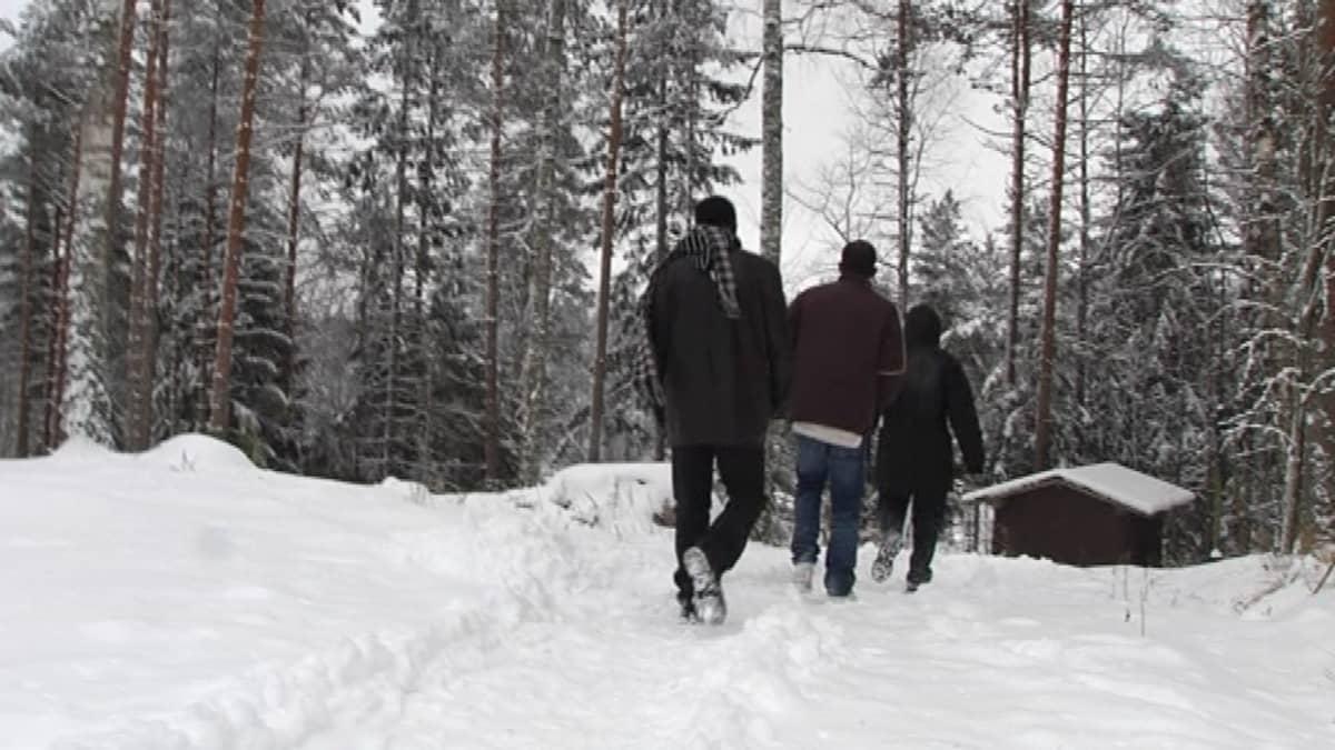 Kolme afrikkalaista miestä kävelee rantasaunalle lumisesa metsässä.
