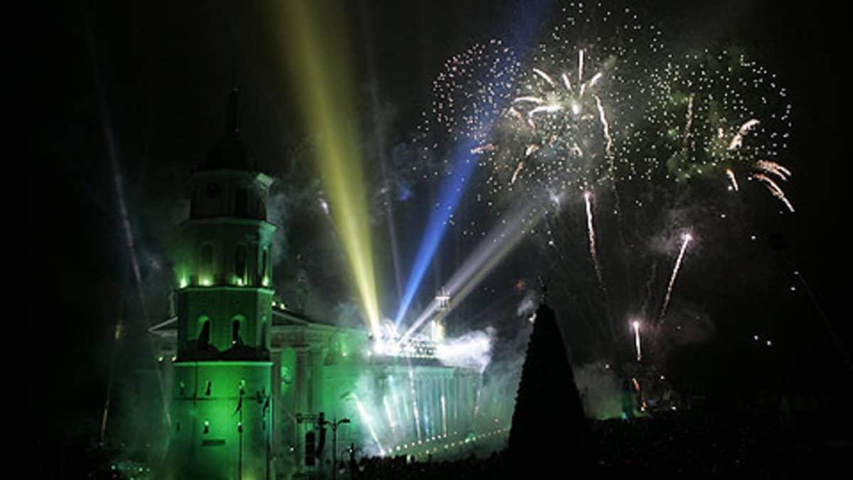 Ilotuliiteita ja sini-valko-keltaisia lasersäteitä Vilnan yötaivaalla