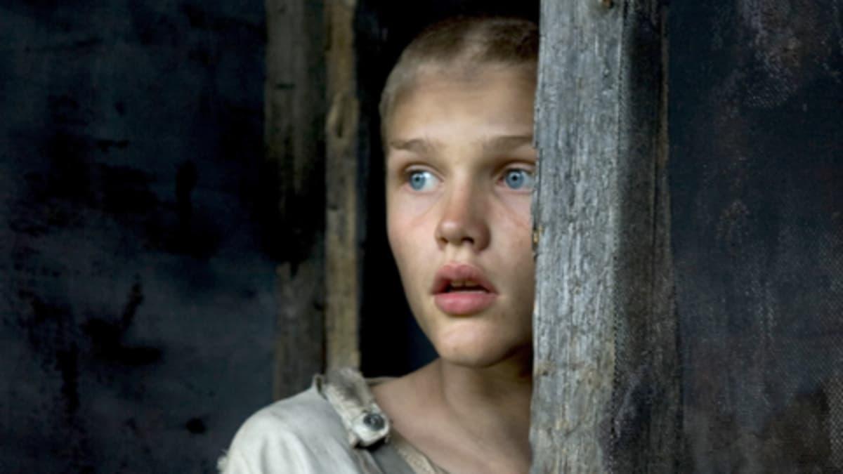 Elokuvan päähenkilö mykkä poika kurkistaa puupalkin takaa