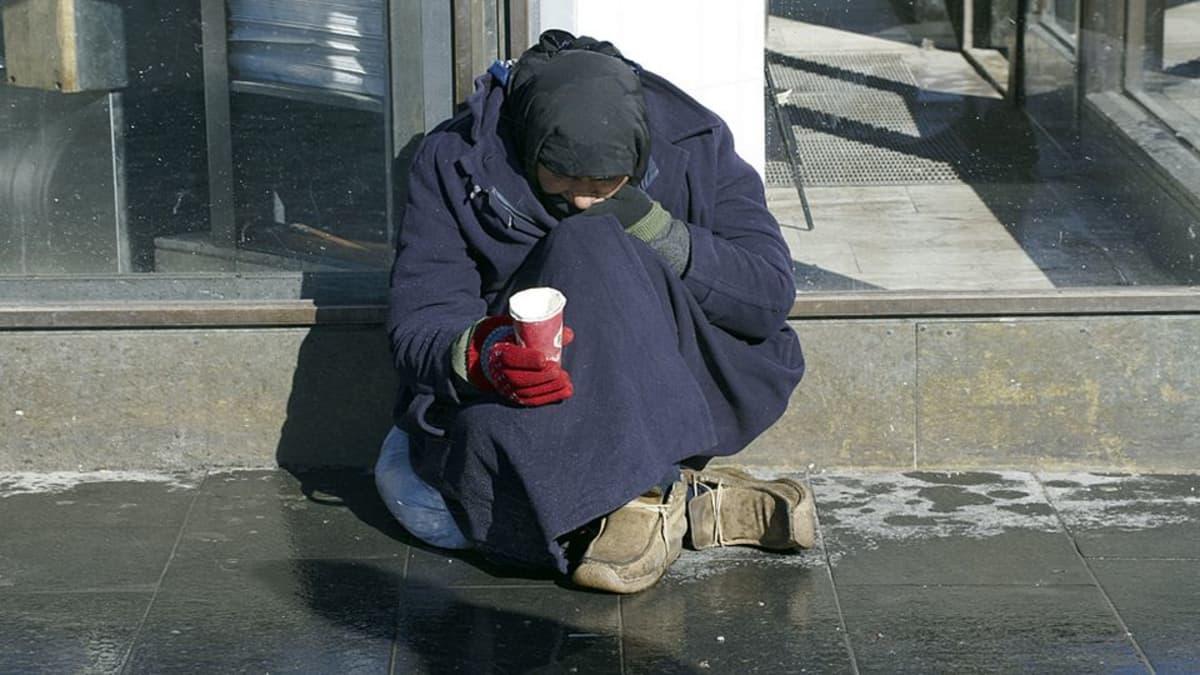 Kerjäläinen istuu kadulla pahvimukiin kerjäten.
