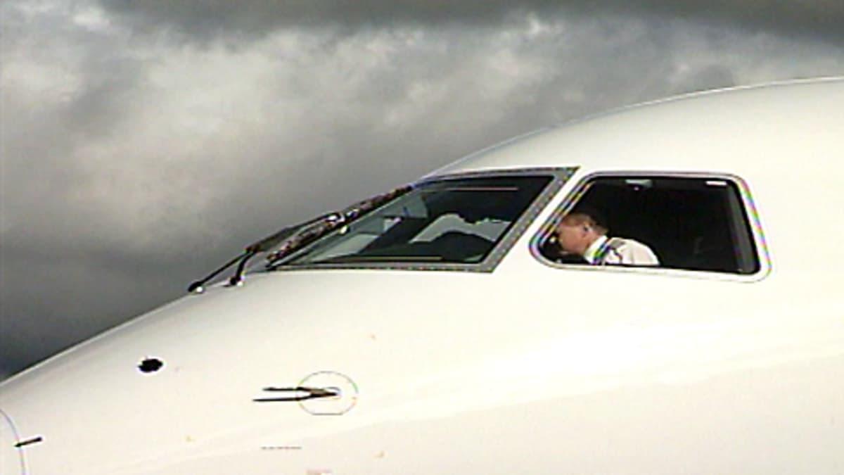 Finnairin lentäjä lentokoneen ohjaamossa.