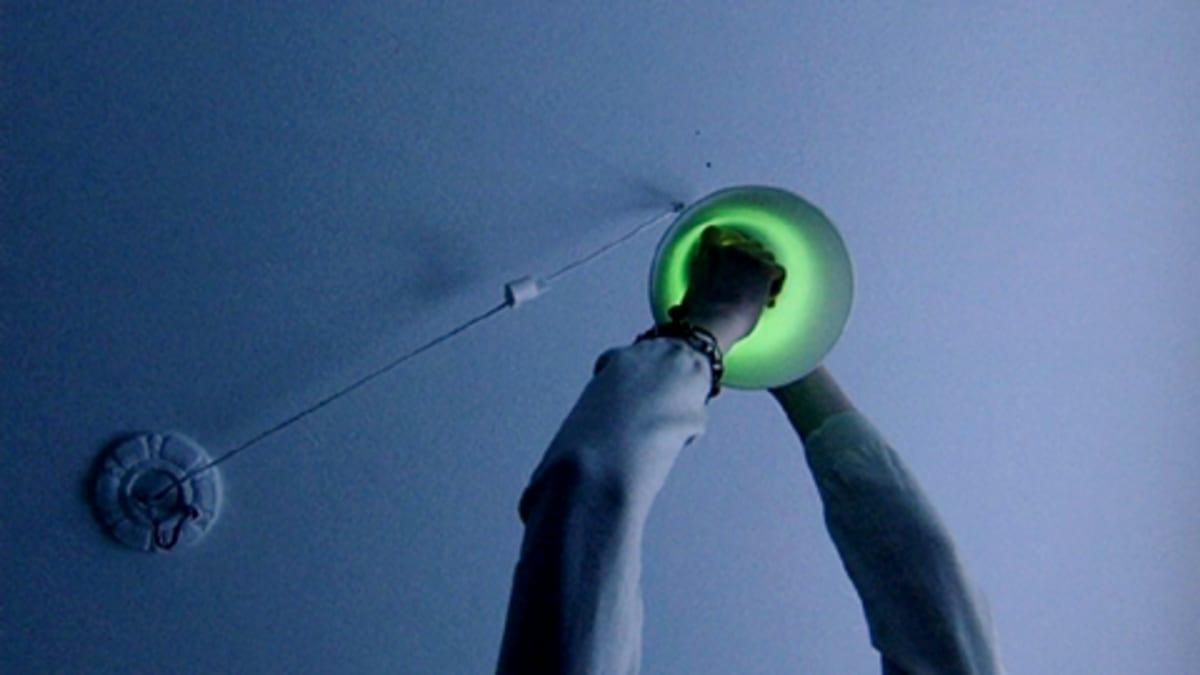 Henkilö vaihtaa hehkulampun tilalle energiansäästölamppua