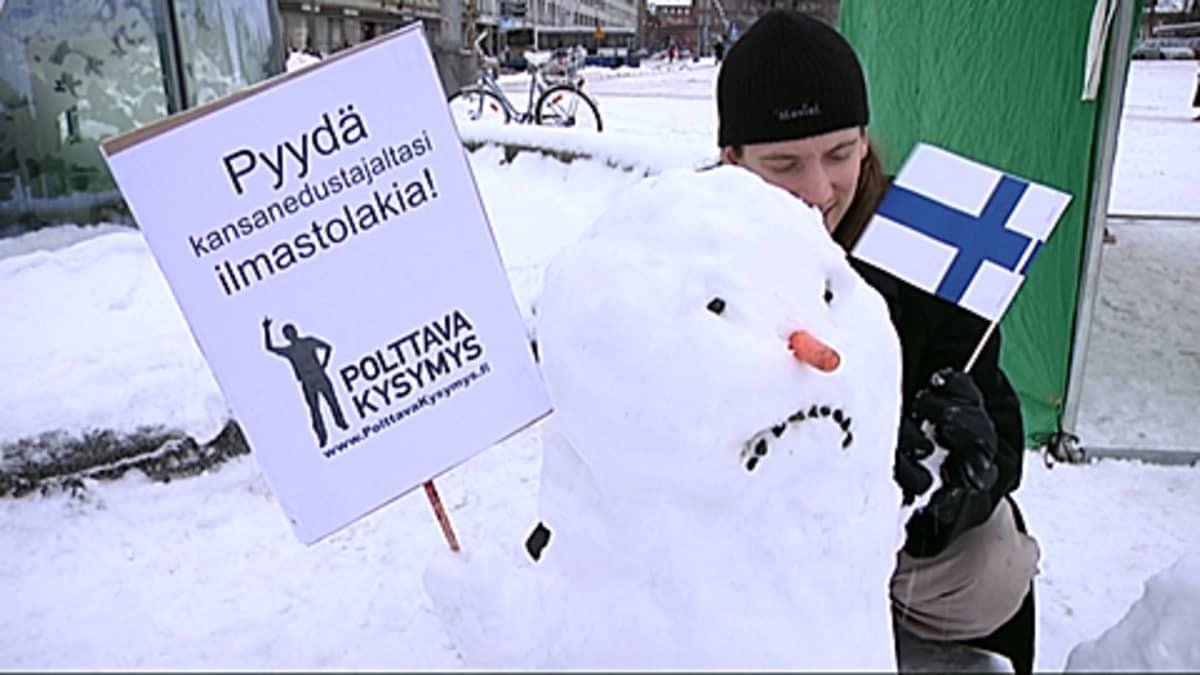 Lumiukko kyltti kourassa.