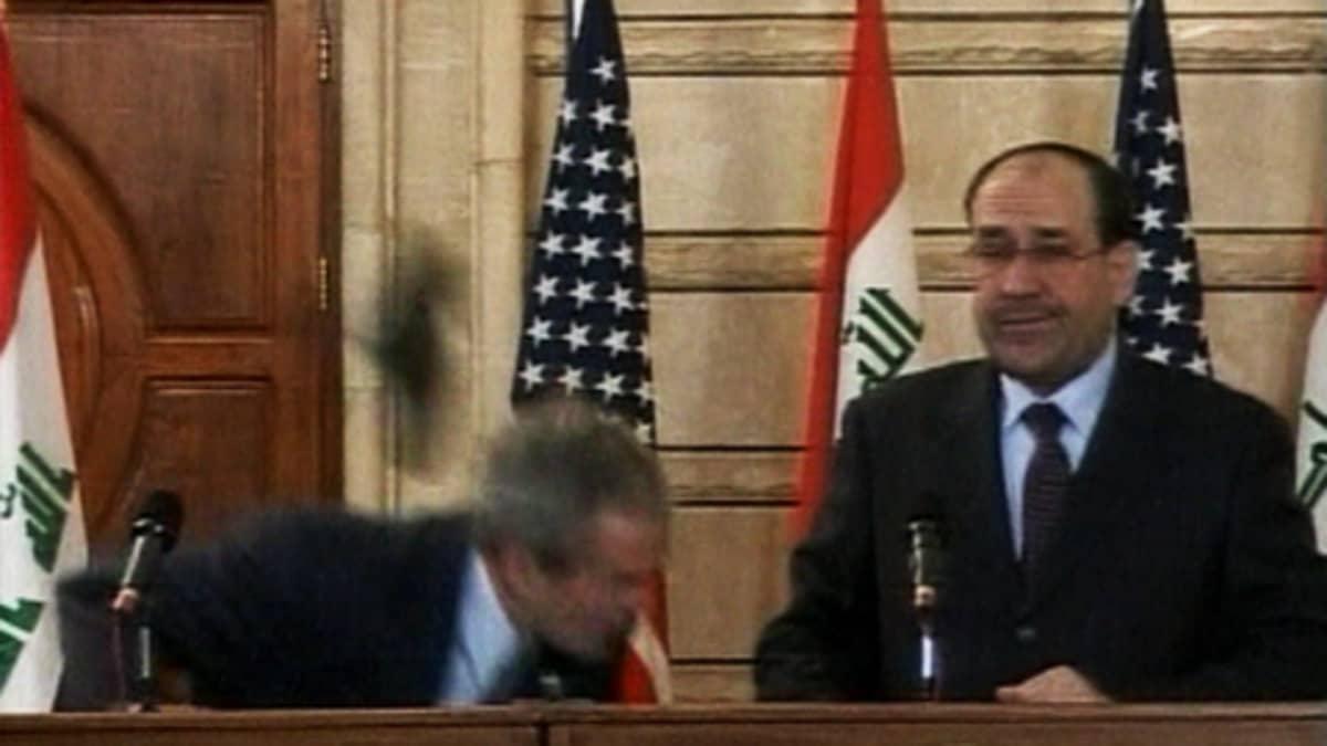 Irakilaistoimittaja heittää George W. bushia kengällään.