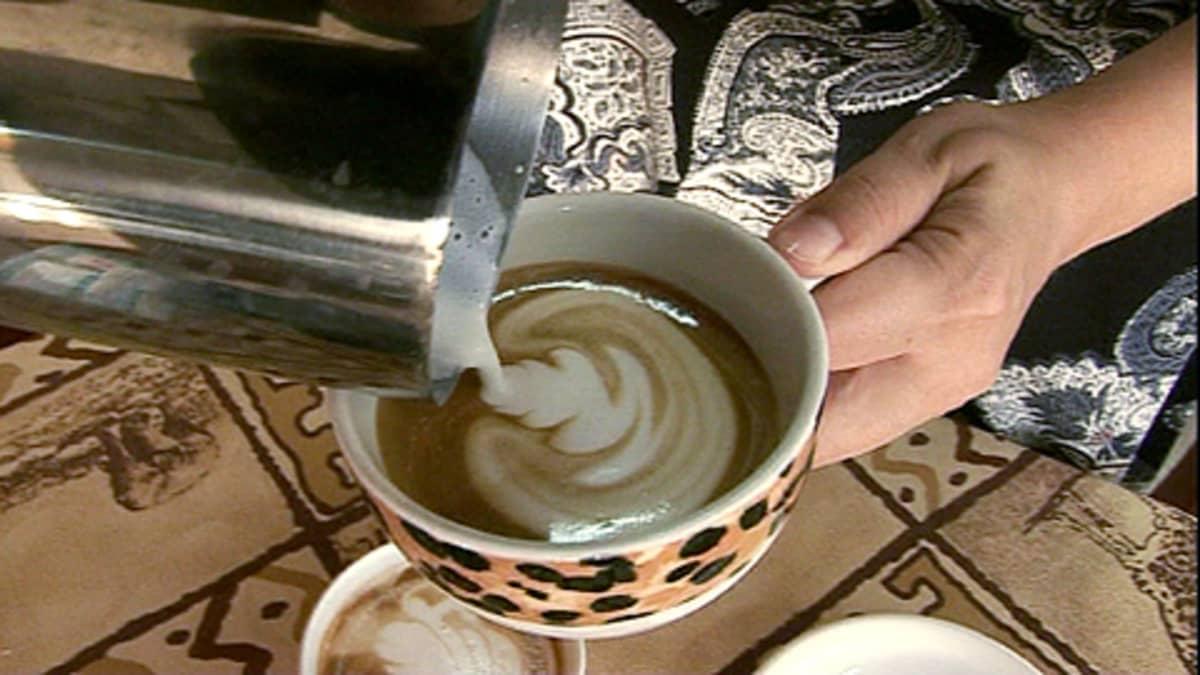 Nainen kaataa maitoa kahvikuppiin