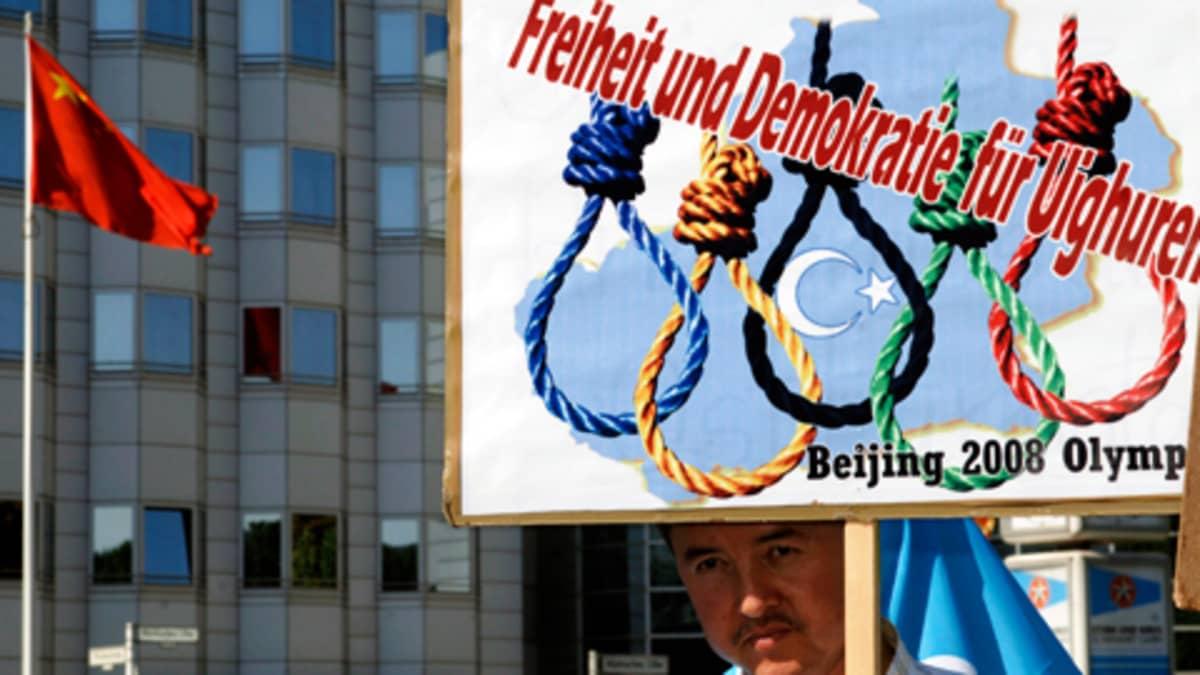 Keski-ikäinen mies jonka kyltissä hirttoköysiä ja teksti 'Freiheit und Demokratie für die Uiguren'.