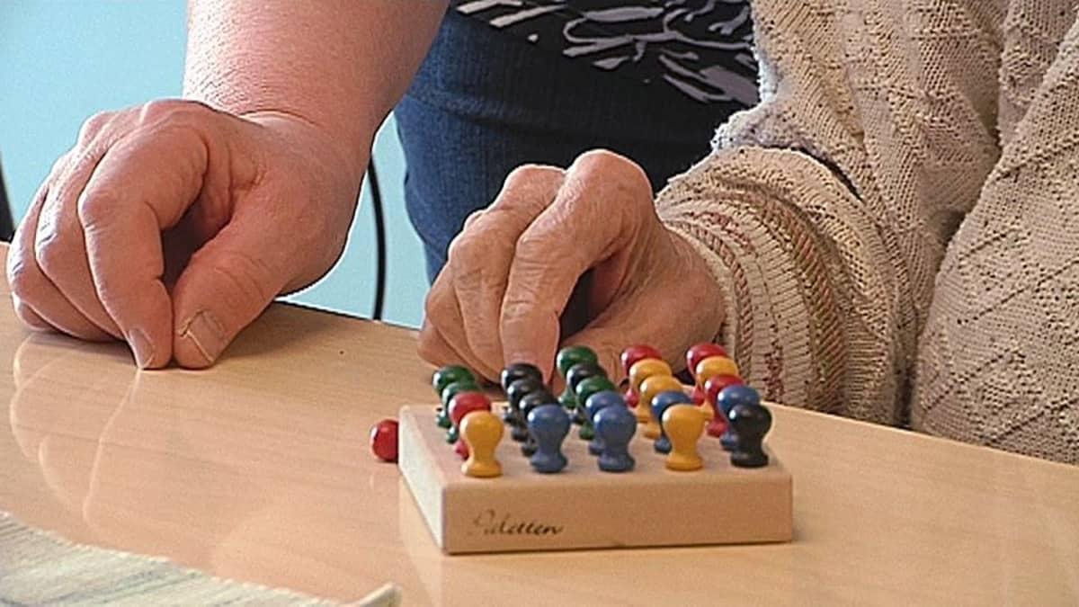 Vanhus ja hoitaja pelaavat pöydän ääressä.