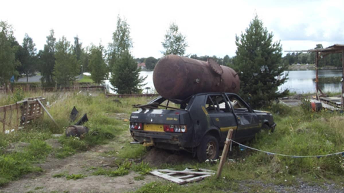 Volvo-merkkinen romuauto, jonka katolle on pudotettu ruosteinen tankki.