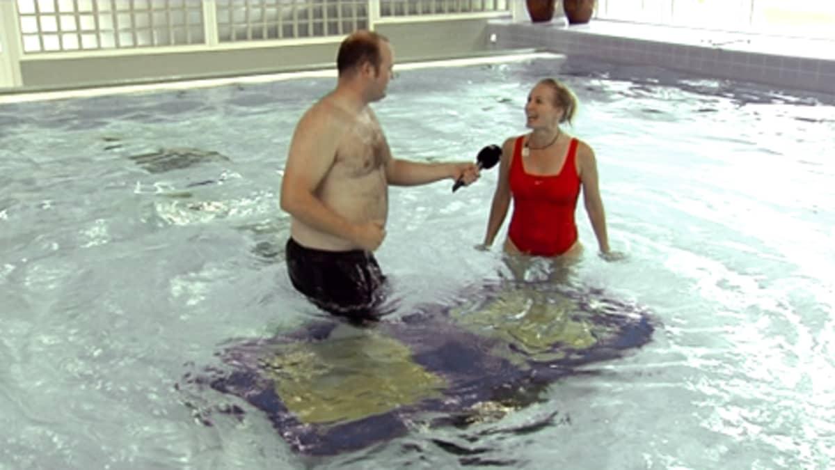 toimittaja haastattelee naista vedessä ja hyppii samalla trampoliinilla