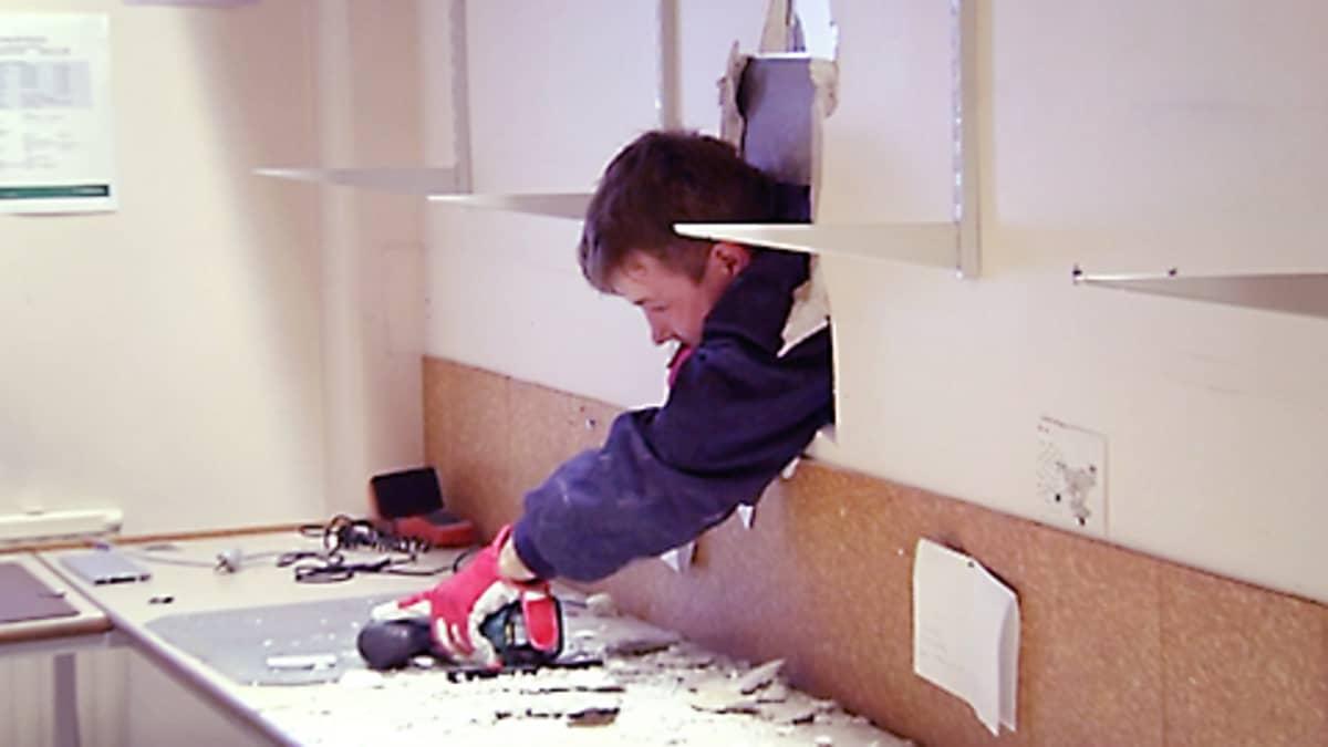 Rakennusmies purkaa seinää.