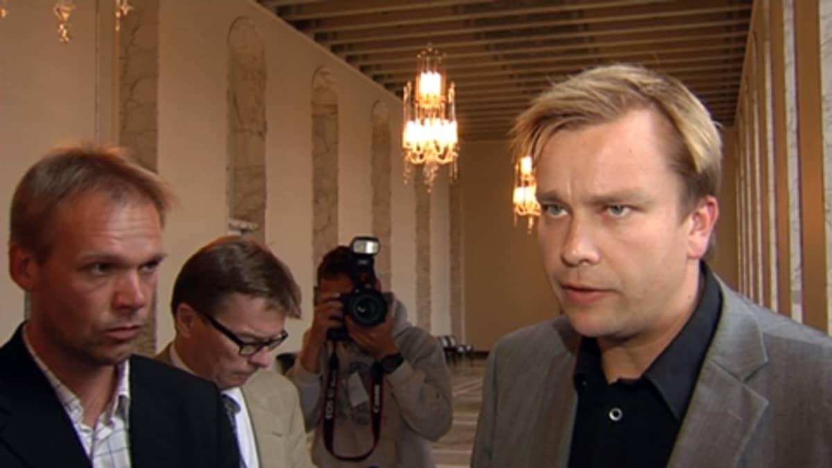 Kansanedustaja Antti Kaikkonen eduskunnan  käytävällä toimittajien ympäröimänä.