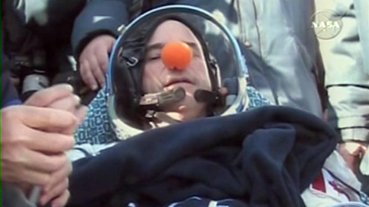 Kanadalainen miljardööri Guy Laliberté laskeutuneena Maan kamaralle. Makuuasennossa ympärillään ihmisiä. Hänen pulssiaan mitataan.
