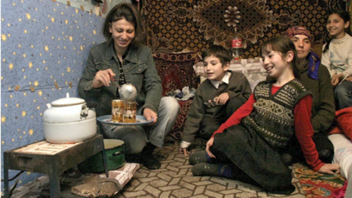 Äiti annostelee ruokaa lapsilleen pakolaisleirissä
