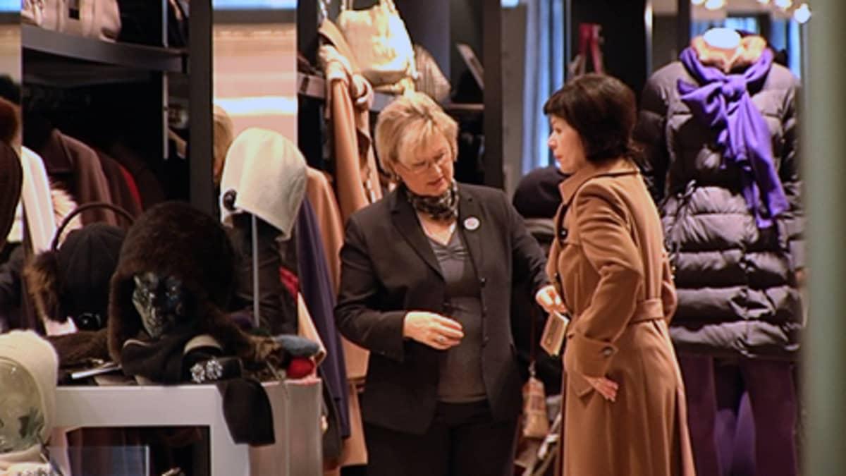 Naisasiakas sovittaa takkia vaateliikkeessä. Myyjä arvioi vieressä.