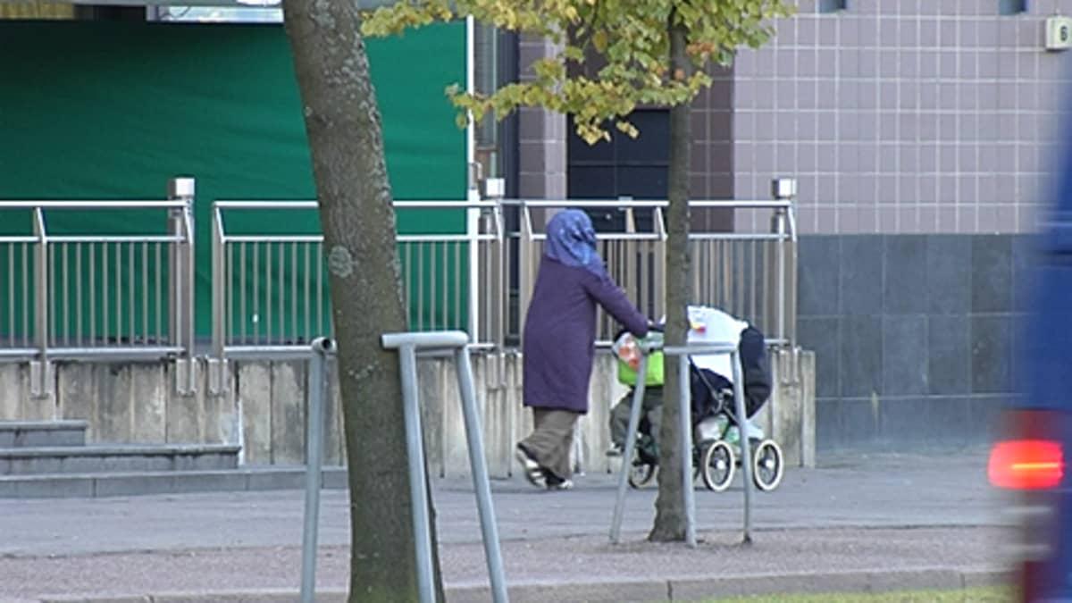 Maahanmuuttajanainen työntää lastenvaunuja kadulla. Auto ajaa ohi.