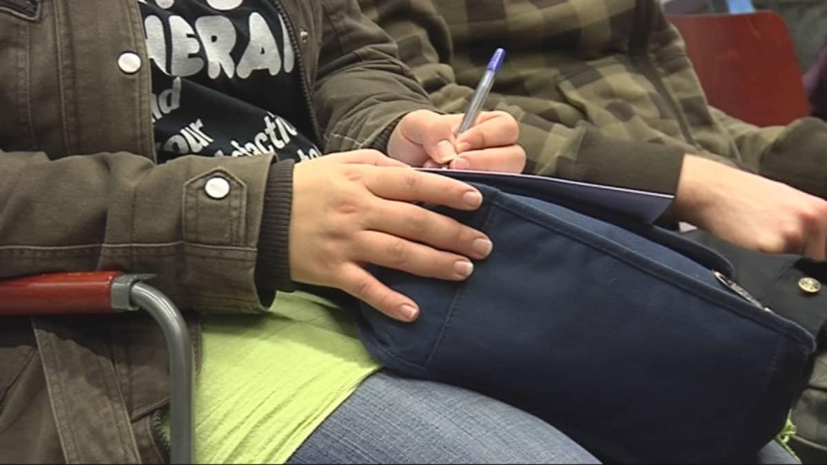 Nuori kynä' ja paperi kädessä.