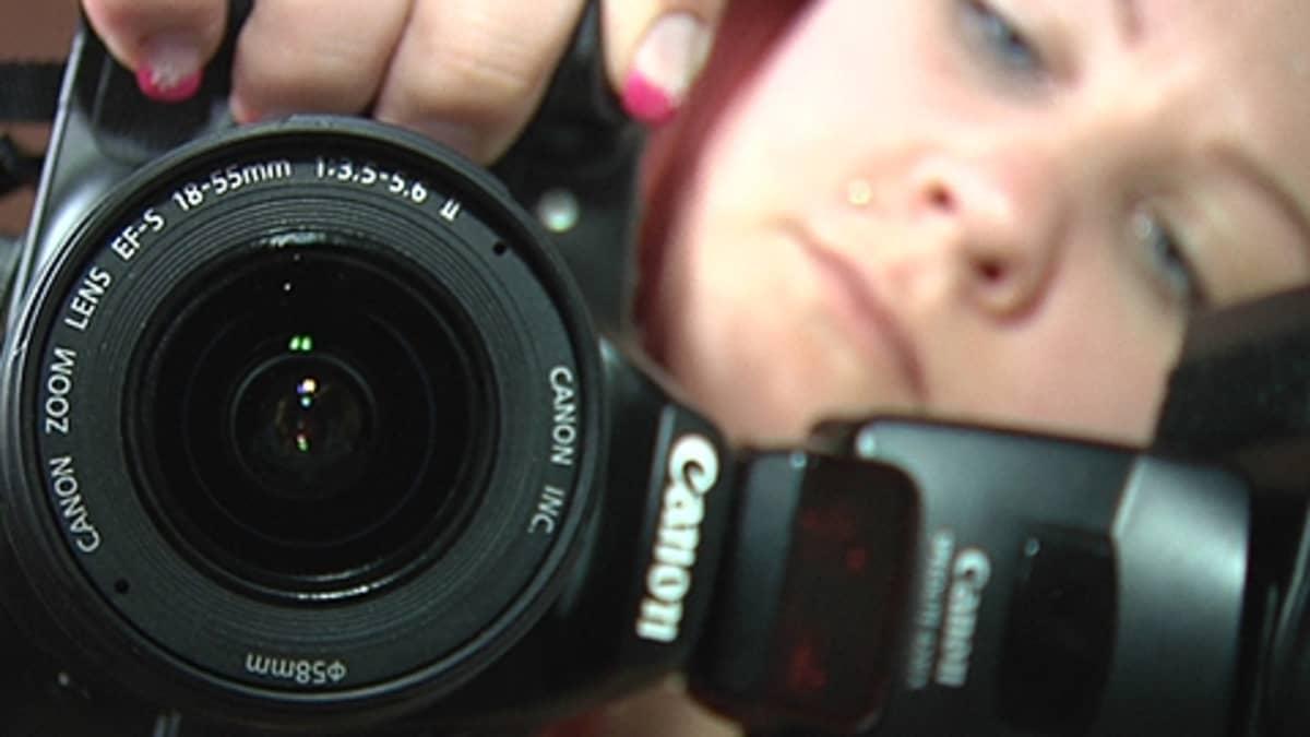 nainen kuvaa kameralla