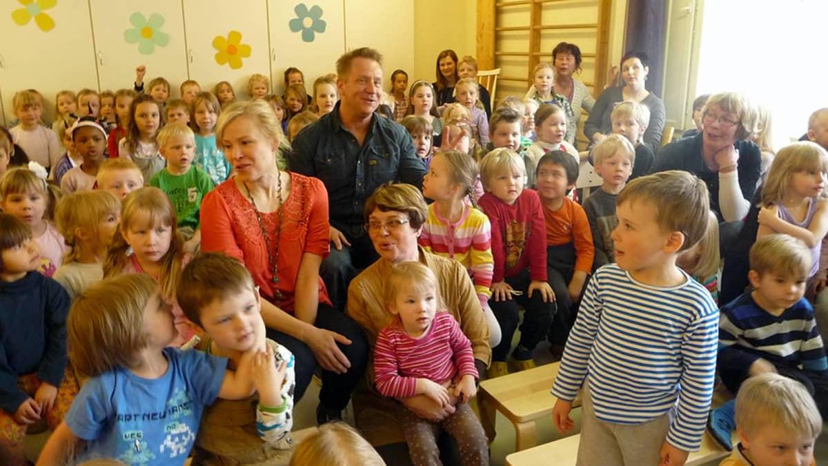 Susanna Hietala ja Olli Lindholm päiväkotilasten ympäröimänä