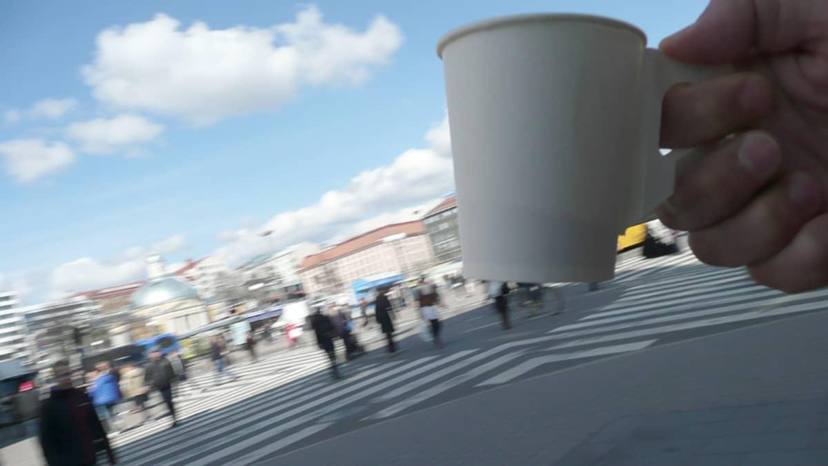 Pahvinen kahvikuppi kädessä.