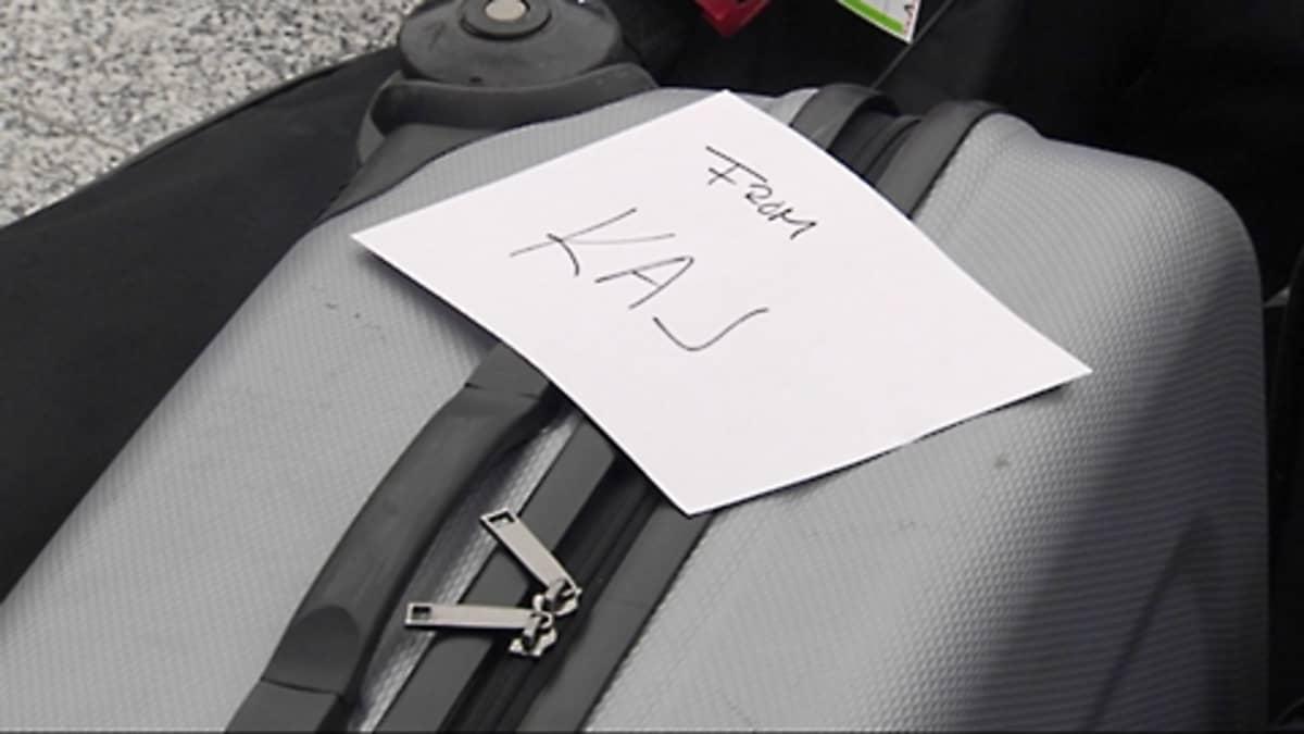 """Matkalaukku, jonka päällä käsin kirjoitettu lappu """"from KAJ"""""""