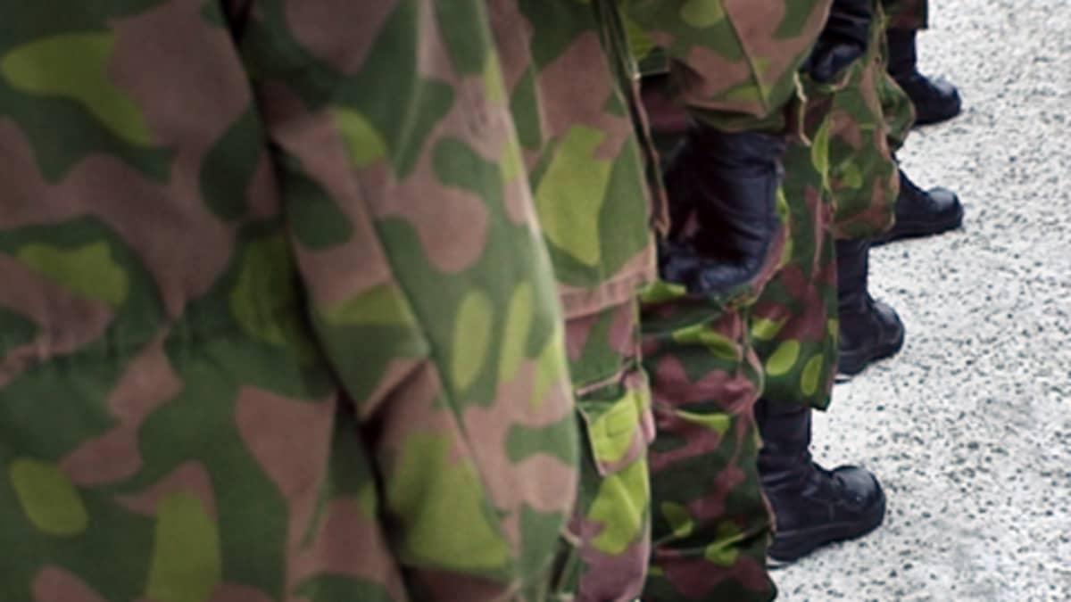 Maastopukuisia sotilaita jonossa.
