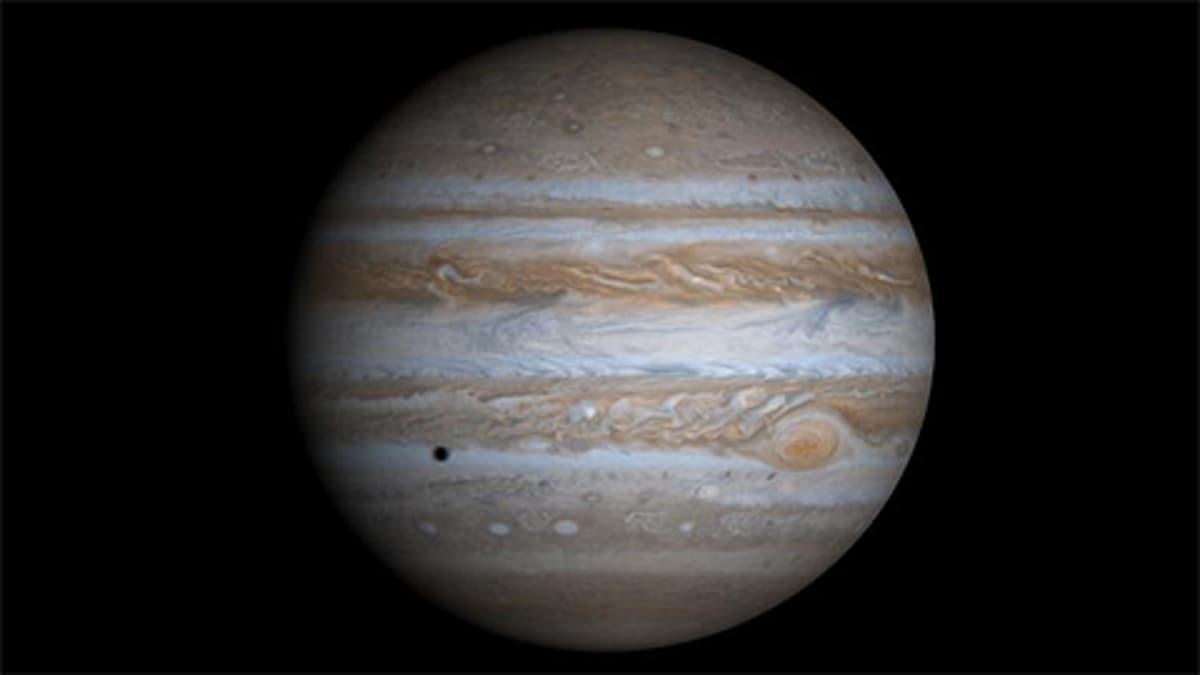 Neljästä Nasan Cassini-luotaimen joulukuussa 2000 ottamasta kuvasta koottu kuva Jupiterista. Kameran kuva-ala ei riitä ottamaan kuvaa koko planeetasta kerralla. Jupiterin Europa-kuu heittää varjon planeetan pinnalle.